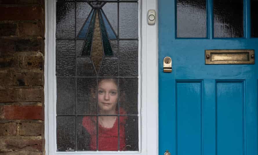 A child stands behind a blue door.