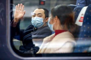 A man waves from the first outbound train leaving Hubei province since the lockdown was ended