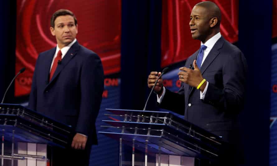 Ron DeSantis looks on as Andrew Gillum makes a point in a debate in Tampa.