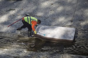 A city worker removes a mattress left by a group of homeless people.