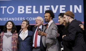 Bernie Sanders sings on stage with performers at a campaign rally in Henderson, Nevada.