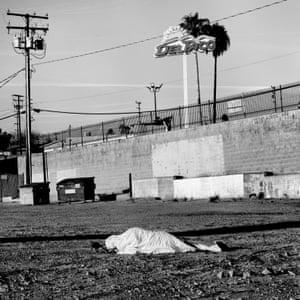 USA. Barstow, California. 2020. A man sleeps in an empty lot.