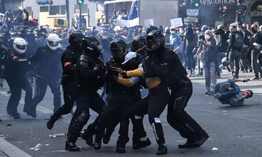 French riot police forces detain a protester.
