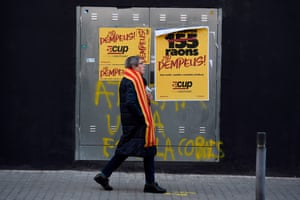 A woman walks by electoral posters outside a polling station in Sabadell
