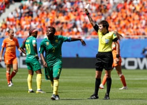 Cameroon's Christine Manie is shown a yellow card by referee Casey Reibelt.