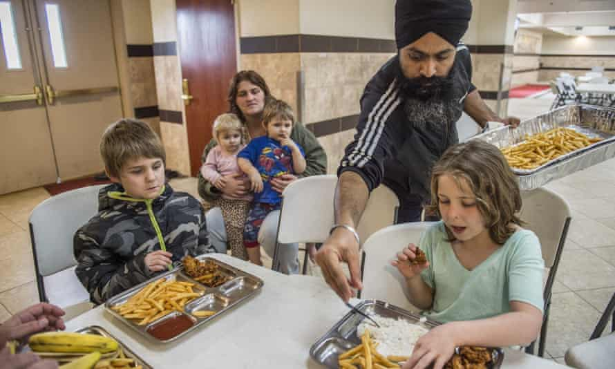 Amarjit Singh, second from right, helps distribute food to members of the Lyon family from Yuba City at the Gurdwara Sahib Sikh Temple in Sacramento.