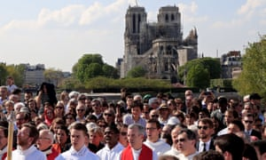 People attend a Good Friday procession along the banks of the River Seine near Notre Dame Cathedral in Paris.
