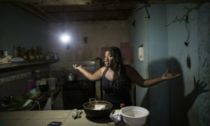 Dugleidi Salcedo complains to a neighbor about the high price of food as she prepares arepas for her three sons in her kitchen in the Petare slum, in Caracas, Venezuela, in February 2019.