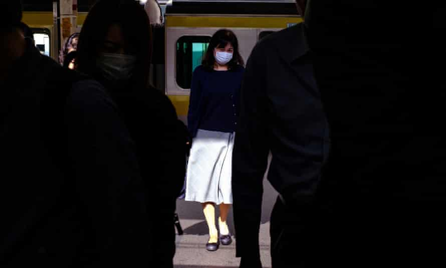 People wearing face masks get off a train at Shinjuku Station in Tokyo