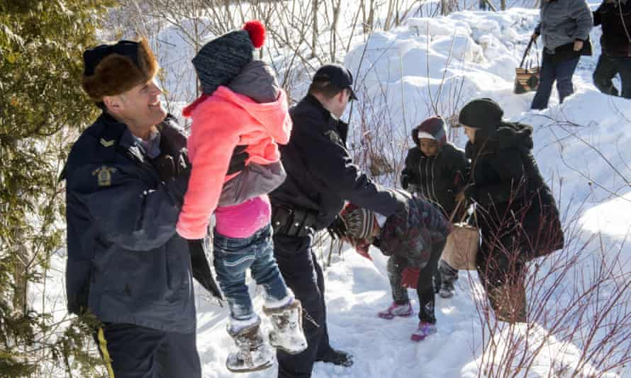 A Somalian family is helped into Canada by Royal Canadian Mounted Police officers in February 2017. During that year, some 2,550 US citizens applied for asylum in Canada.