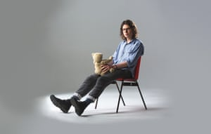 Comedian Simon Amstell sitting in a chair, holding a teddy bear