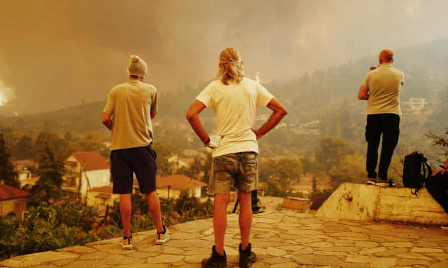 Residents of Gouves on the Greek island of Evia watch as wildfires spread towards their homes.