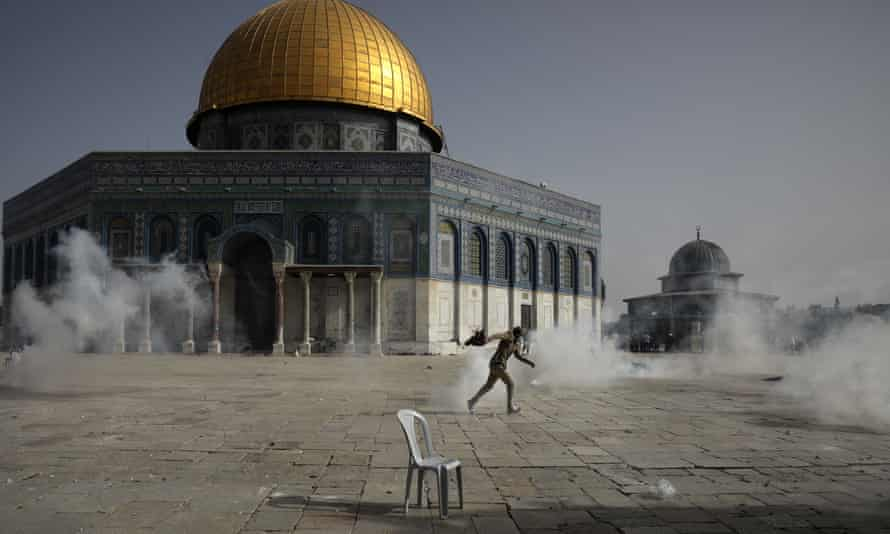 A Palestinian man runs away from teargas during clashes with Israeli security forces in front of the Dome of the Rock.