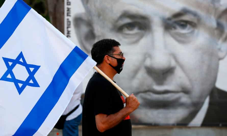 A protester carries the Israeli flag in front of a poster of Benjamin Netanyahu