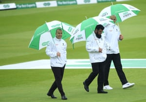 The umpires inspect the pitch before calling a halt to day one of the second Ashes Test