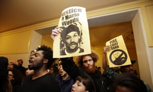 Demonstrators hold signs outside of a crowded police commission hearing inside city hall on Wednesday.