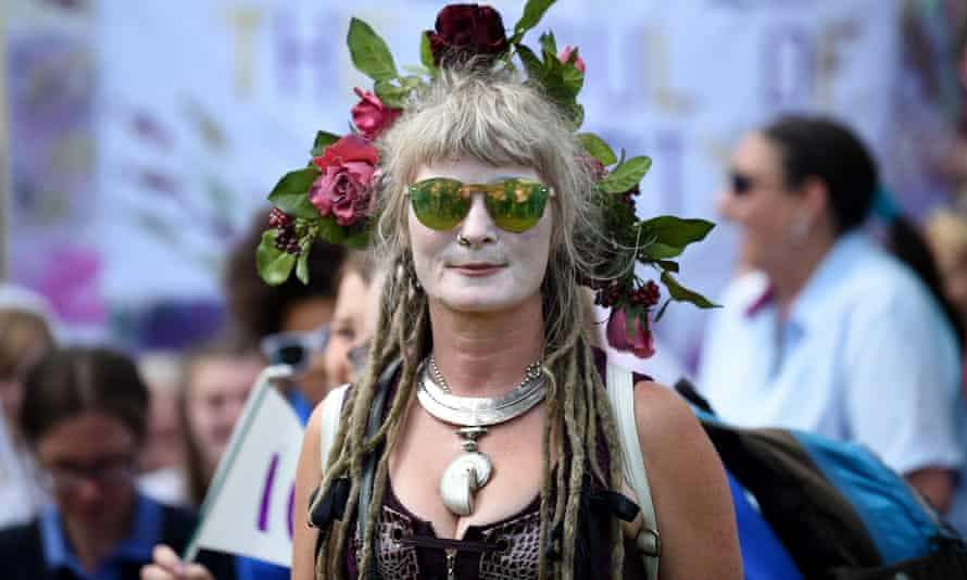 A woman with her face painted white joins marchers as they gather on the Meadows ahead of the march in Edinburgh