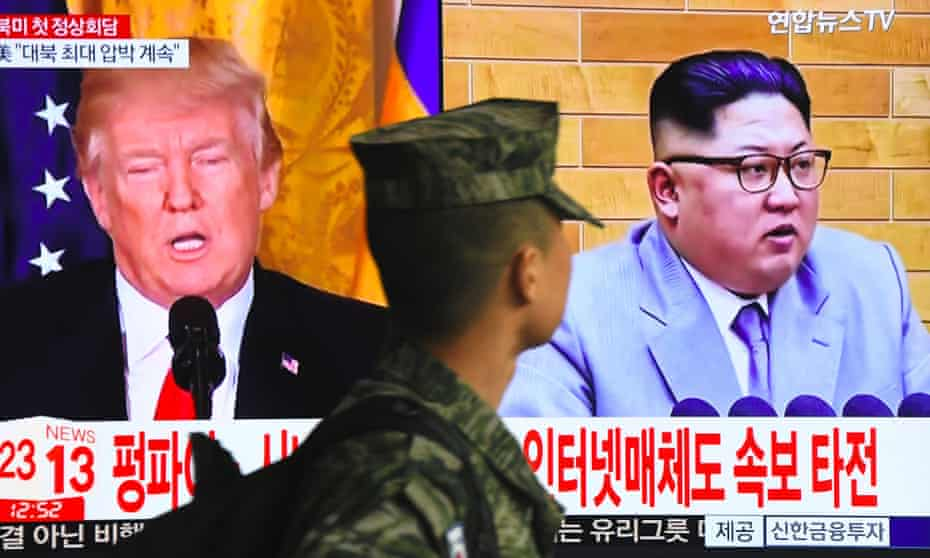 A South Korean soldier walks past a television screen showing pictures of US President Donald Trump and North Korean leader Kim Jong Un at a railway station in Seoul.