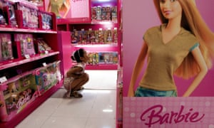 Child in a toy store looking at Barbie boxes.