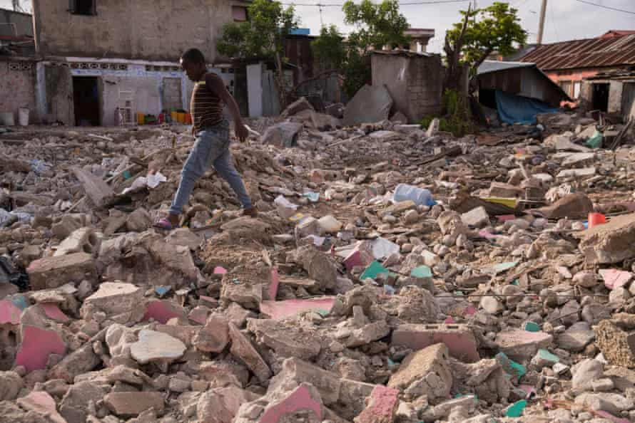 A boy walks over the rubble of a house.