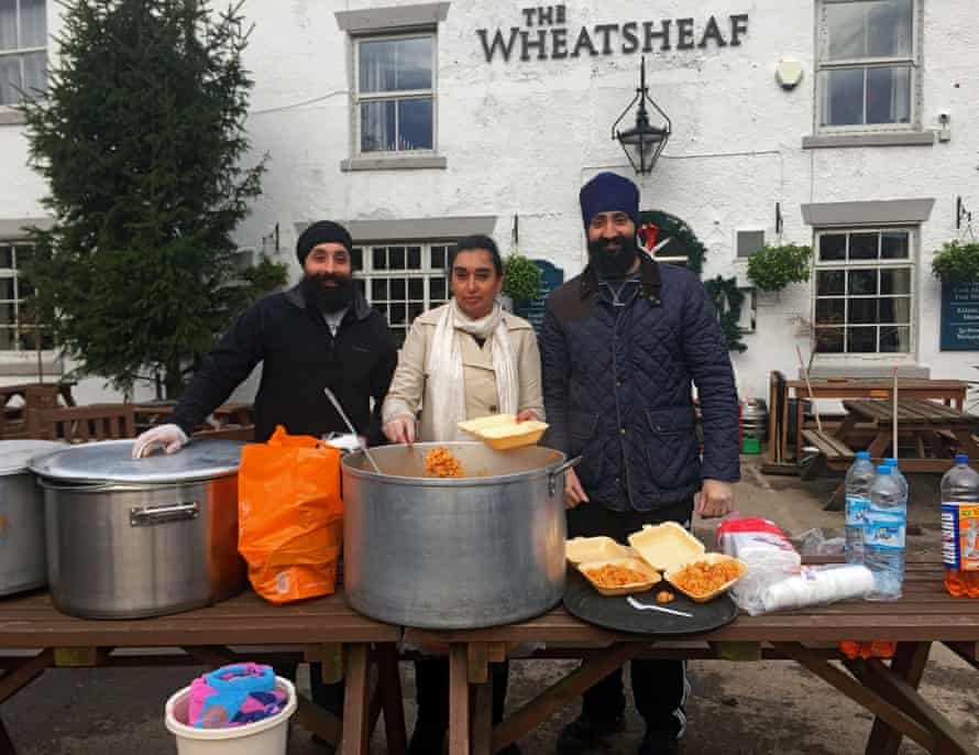 Volunteers from Khalsa Aid, giving out food to villagers in the flood-hit Lancashire village of Croston.