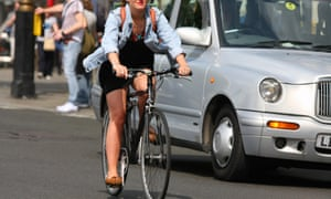 A woman riding a bicycle next to a taxi in London
