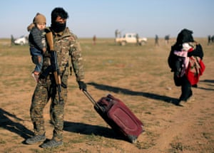 A fighter from Syrian Democratic Forces (SDF) holds a baby near the village of Baghouz