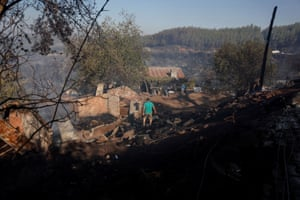 A man walks among ruins of a burnt house in the Mezargedigi area of Marmaris, Turkey