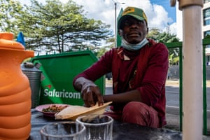 Charles Lumba, a matatu conductor, takes his mask off to eat lunch while taking a break at a roadside restaurant