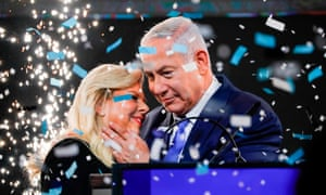 Israeli PM Benjamin Netanyahu embraces his wife Sara as confetti is blown at his appearance before supporters in Tel Aviv.