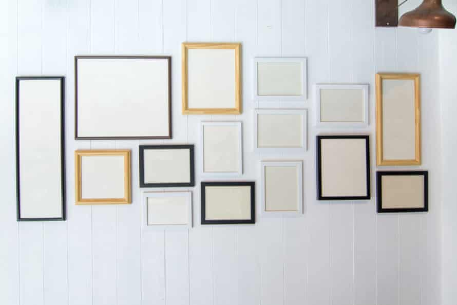 Empty frames hang on  a white wall