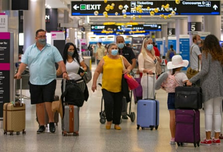 Travelers wearing protective face masks walking through concourse D at the Miami international airport in Miami, Florida, last month.