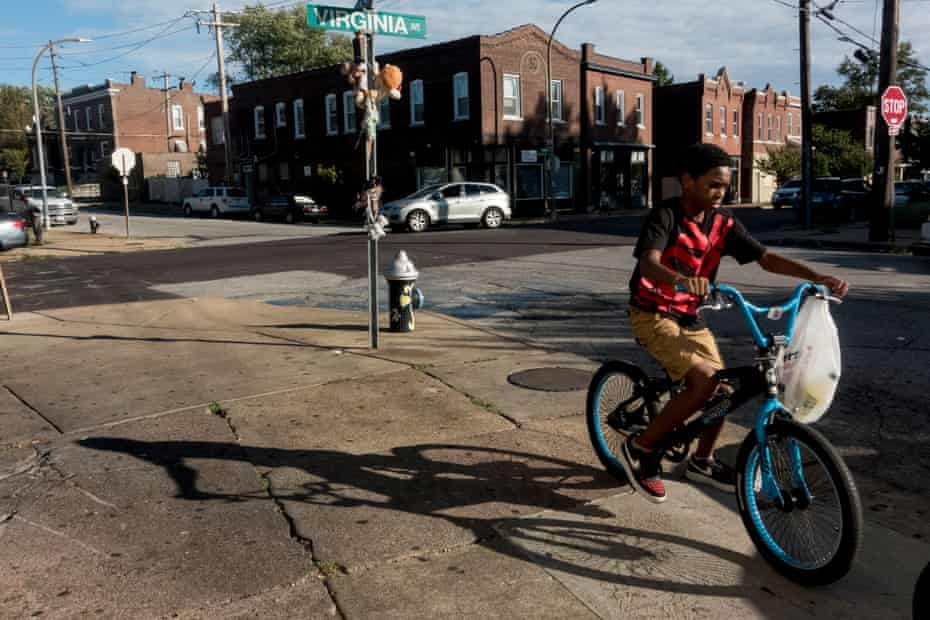 A boy rides his bike past a makeshift memorial of stuffed animals for a homicide victim in south St Louis on 13 September.