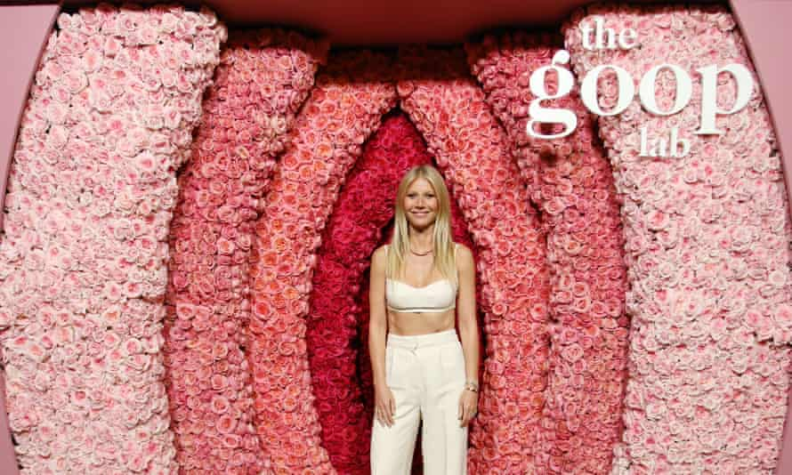 Gwyneth Paltrow surrounded by suggestively arranged pink flowers