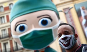 A man wearing a protective face mask poses for pictures next to an oversized model of a health worker in Madrid.