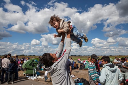A father plays with his daughter while waiting to board a bus at the Serbian-Hungarian border.