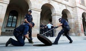 Officers from Catalonia's regional police force, Mossos D'esquadra, search under a manhole cover outside the regional assembly in Barcelona on Tuesday.