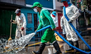 Municipal workers clean and disinfect the surroundings of the Caqueta market in the north of Lima.