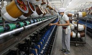Worker on glass fibre production line in Jiujian, China