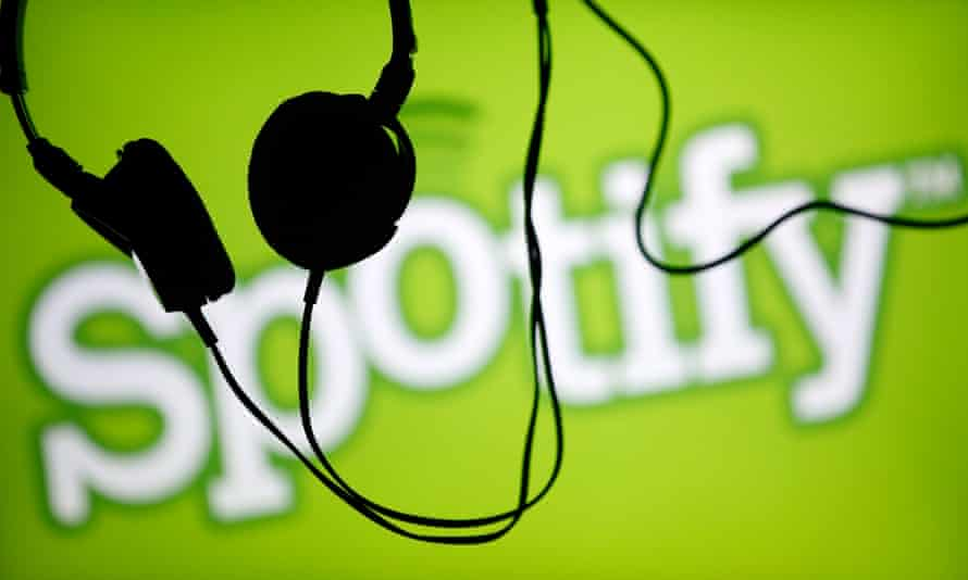 Headsets hang in front of a screen displaying a Spotify logo on it.