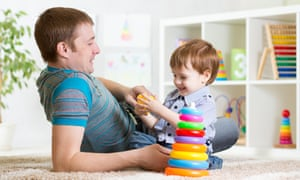 Happy father and child son playing together on a carpet in the front room, a tower of multi-coloured plastic rings in the foreground