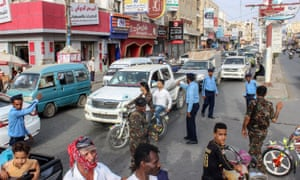 Yemeni policemen (in blue) and Houthi fighters controlling traffic in Hodeidah.