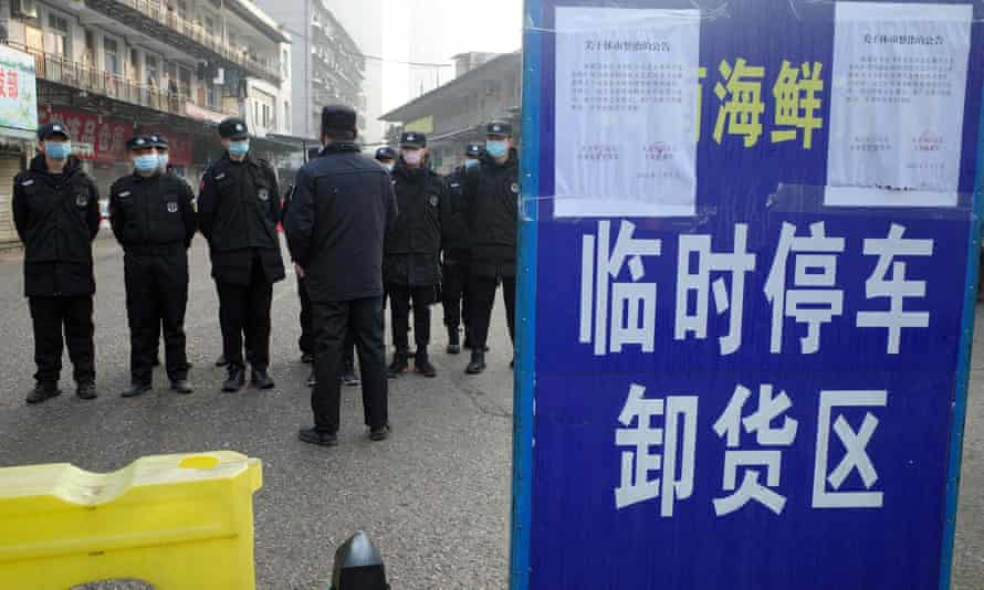 File photo shows security guards standing in front of the seafood market in Wuhan, where Covid-19 is believed to have originated.