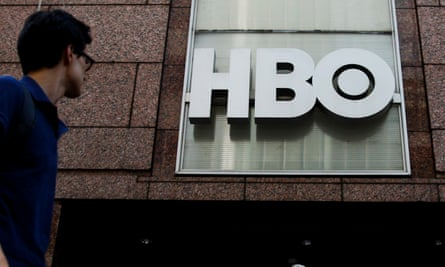 a man looking at the HBO sign on the side of a building