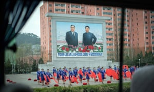Women rehearse a routine with flags, in front of a large mural of former leaders Kim Il-sung and Kim Jong-il.