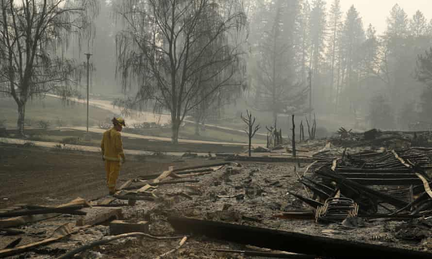 A firefighter searches for human remains in a trailer park destroyed in the Camp fire.