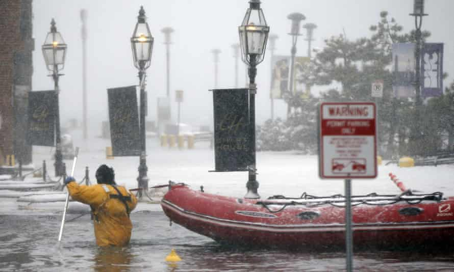 A firefighter wades through waters from Boston Harbor, which flooded onto Long Wharf on 4 January 2018.