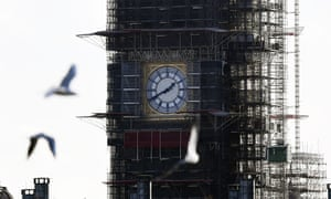 Close up of Big Ben under scaffolding with birds flying in the foreground
