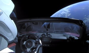 A cherry red Tesla Roadster automobile floats through space after it was carried there by SpaceX's Falcon Heavy.