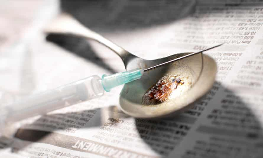 Hypodermic needle and syringe with a pile of heroin on a spoon